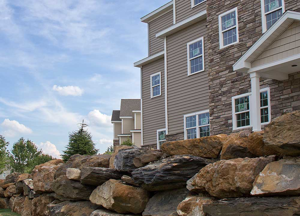 Large stone retainer wall next to apartment building