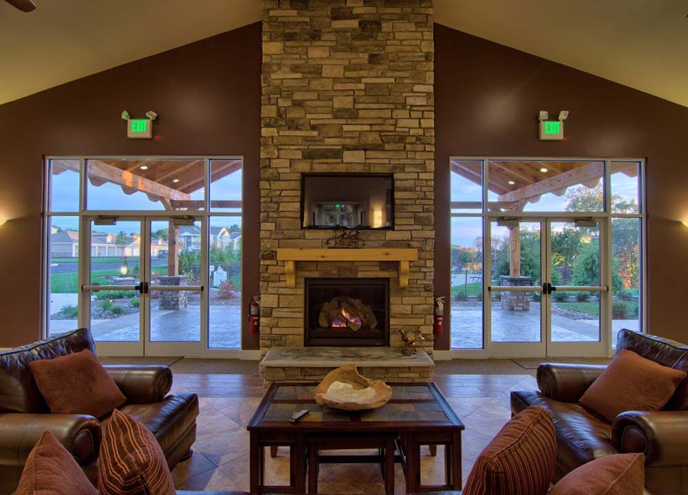 indoor fireplace with large windows and chairs